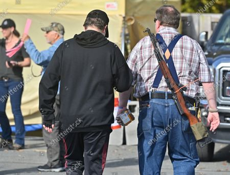A man wears a long gun on his back and carries bullets while attending the Freedom Fest. The Rod of Iron Freedom Festival is an anti-government, Christian far-right movement that held a 3 day 2nd Amendment Rally of Freedom, Faith and Family. A few far right politicians were in attendance and the event featured a speech from HJ Sean Moon, the founder of the  World Peace and Unification Church in Pennsylvania, who often wears a crown made of bullets. Members take marriage vows to their AR-15 rifles and have blessings for their guns. Many in attendance were seen carrying guns.