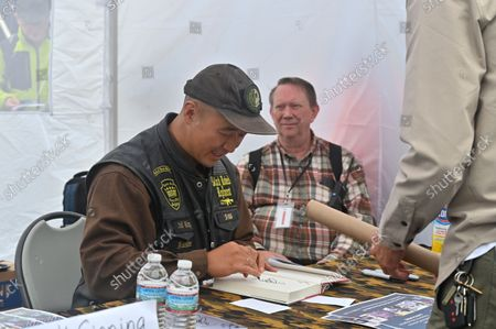 """Hyung Jin """"Sean"""" Moon, signs a copy of his book. Moon and his wife started the Pennsylvania-based World Peace and Unification Sanctuary Church, an unofficial offshoot and sect of the Unification movement and run the Rod of Iron Ministries. The Rod of Iron Freedom Festival is an anti-government, Christian far-right movement that held a 3 day 2nd Amendment Rally of Freedom, Faith and Family. A few far right politicians were in attendance and the event featured a speech from HJ Sean Moon, the founder of the  World Peace and Unification Church in Pennsylvania, who often wears a crown made of bullets. Members take marriage vows to their AR-15 rifles and have blessings for their guns. Many in attendance were seen carrying guns."""
