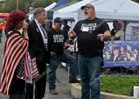 Representative Rick Saccone and his wife Yong speak with Teddy Daniels a politician running for congress that mocked Capitol Police, both politicians attended the Rod of Iron ministry Freedom Fest. Daniels was at the January 6th insurrection. The Rod of Iron Freedom Festival is an anti-government, Christian far-right movement that held a 3 day 2nd Amendment Rally of Freedom, Faith and Family. A few far right politicians were in attendance and the event featured a speech from HJ Sean Moon, the founder of the  World Peace and Unification Church in Pennsylvania, who often wears a crown made of bullets. Members take marriage vows to their AR-15 rifles and have blessings for their guns. Many in attendance were seen carrying guns.