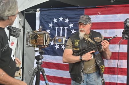 A man holding an automatic rifle poses in front of a 3% flag which is a far-right anti-government militia movement. The Rod of Iron Freedom Festival is an anti-government, Christian far-right movement that held a 3 day 2nd Amendment Rally of Freedom, Faith and Family. A few far right politicians were in attendance and the event featured a speech from HJ Sean Moon, the founder of the  World Peace and Unification Church in Pennsylvania, who often wears a crown made of bullets. Members take marriage vows to their AR-15 rifles and have blessings for their guns. Many in attendance were seen carrying guns.