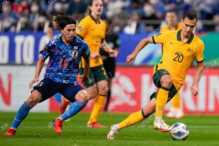 Stock Image of Australia's Trent Sainsbury, right, and Japan's Takumi Minamino compete for the ball during the World Cup 2022 group B qualifying soccer match between Australia and Japan at Saitama Stadium in Saitama, north of Tokyo