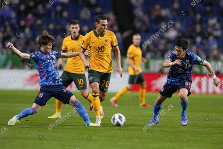 Stock Photo of Australia's Trent Sainsbury, centre, competes for the ball with Japan's Kyogo Furuhashi, left, and Wataru Endo during the World Cup 2022 group B qualifying soccer match between Australia and Japan at Saitama Stadium in Saitama, north of Tokyo
