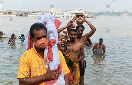 Hindu priest and devotees coming out of Ganges water after performing Hindu ritual called Nabapatrika or Kola Bou snan on the morning of Maha Saptami, the second day of Durga puja celebration. Though it is pandemic time, most of the people are not wearing any protective mask.
