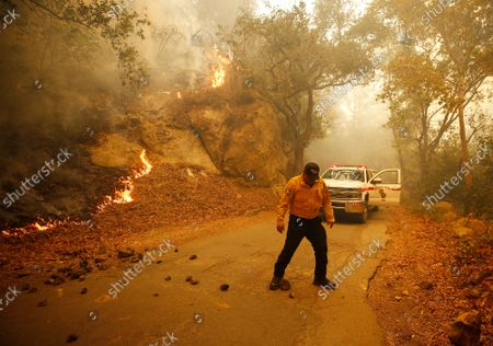 Cal Fire Battalion Chief Michael Martinez kicks rocks off Refugio Road near Circle Bar B guest ranch as flames from the Alisal Fire create rock slides Tuesday afternoon as the Alisal Fire is over 7,000 acres on Tuesday after it quickly grew Monday afternoon driven by sundowner winds as it burned through Tajiguas Canyon to the 101 freeway forcing its closure. Mandatory evacuations are in place as the gusty winds drive flames through rough terrain that hasn't burned in decades. The 1955 Refugio Fire that consumed 80,000 acres is the last time much of the area had burned. The historic Reagan Rancho del Cielo which sits near the top of Refugio Canyon could be threatened by the flames as the fire moves into Refugio Canyon. Refugio Road on Tuesday, Oct. 12, 2021 in Gaviota Coast, CA. (Al Seib / Los Angeles Times).