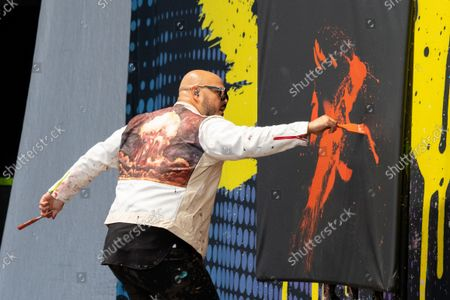 David Garibaldi, a performance painter, paints a portrait of Jimi Hendrix at the Germania Insurance Amphitheater