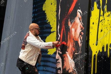Stock Picture of David Garibaldi, a performance painter, paints a portrait of Jimi Hendrix at the Germania Insurance Amphitheater