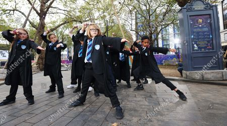 Stock Image of A dazzling installation of Wizarding World wands is unveiled in Leicester Square by Paul Harris, the wand choreographer for Harry Potter and the Order of the Phoenix, hosting a wand lesson for children from Park View Haringey School. The display has launched in partnership with Discover Leicester Square to celebrate the 20th Anniversary of the Harry Potter and the Philosopher's Stone film, which returns to UK and Ireland cinemas on 29th October