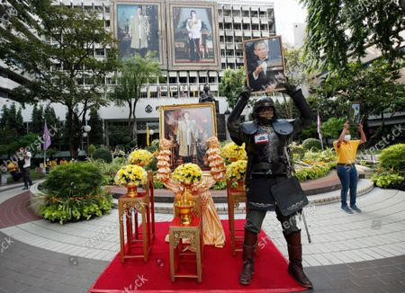 Retired Thai government officer Adul Ittipatanan, dressed as an ancient war lord, holds up a photograph of the late Thai King Bhumibol Adulyadej to mark his fifth death anniversary at Siriraj hospital in Bangkok, Thailand, 13 October 2021. King Bhumibol died at the age of 88 in Siriraj hospital on 13 October 2016 after 70 years of reigning on the throne.