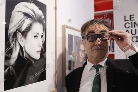 French photographer Luc Roux poses next to a photography of French actress Catherine Deneuve during the inauguration of an exhibition in the framework of the 27th French Film Festival in Malaga, at Alianza Francesa academy in Malaga, Andalusia, Spain, 13 October 2021.