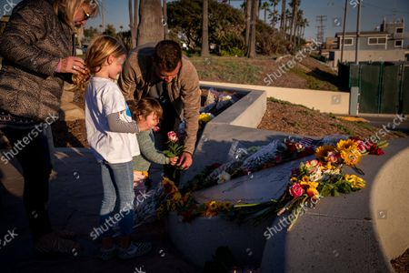 Kyle Simington, right, son-in-law, helps Florence Simington, 2, place a flower at a heart-shaped memorial for grandmother Michele Daschbach Fast, who was one of 8 victims of the Seal Beach massacre at Salon Meritage, as families and friends of victims of Scott Dekraai, the worst mass killer in Orange County history, during a memorial on the 10th anniversary of the massacre at Eisenhower Park in view of the Seal Beach Pier Tuesday, Oct. 12, 2021. (Allen J. Schaben / Los Angeles Times)
