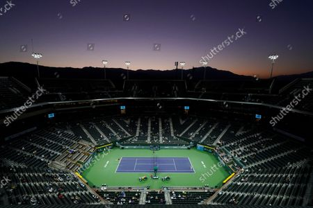 The sun sets as Shelby Rogers and Jelena Ostapenko, of Latvia, play a match at the BNP Paribas Open tennis tournament, in Indian Wells, Calif