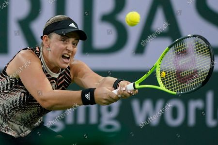 Jelena Ostapenko, of Latvia, returns a shot to Shelby Rogers at the BNP Paribas Open tennis tournament, in Indian Wells, Calif