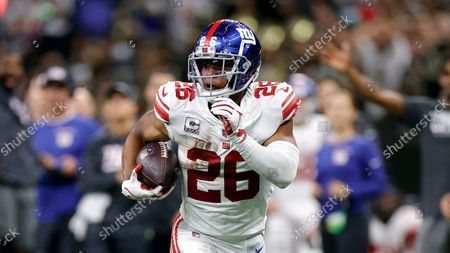 Stock Image of New York Giants running back Saquon Barkley (26) runs the ball during an NFL football game against the New Orleans Saints, in New Orleans
