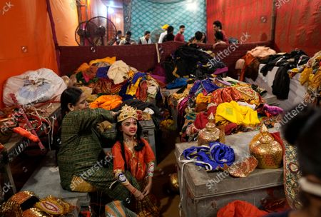 Woman helps a child get dressed to perform a part in a religious play enacting the life of Hindu god Rama during Dussehra festival in New Delhi, India, . The Hindu festival of Dussehra commemorates the triumph of Lord Rama over the demon king Ravana, marking the victory of good over evil