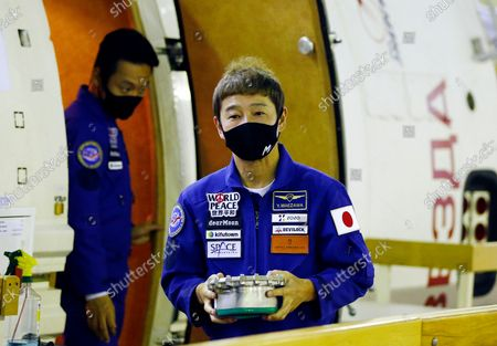 Space flight participant Yusaku Maezawa, foreground, attends a training ahead of the expedition to the International Space Station, at the Gagarin Cosmonauts' Training Center in Star City outside Moscow, Russia, . A Japanese fashion tycoon who's booked a SpaceX ride to the moon is going to try out the International Space Station first. Yusaku Maezawa announced that he's bought two seats on a Russian Soyuz capsule. He'll blast off in December on the 12-day mission with his production assistant and a professional cosmonaut
