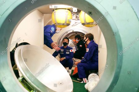 Space flight participants Yusaku Maezawa and Yozo Hirano attend a training ahead of the expedition to the International Space Station at the Gagarin Cosmonauts' Training Center in Star City outside Moscow, Russia, . A Japanese fashion tycoon who's booked a SpaceX ride to the moon is going to try out the International Space Station first. Yusaku Maezawa announced that he's bought two seats on a Russian Soyuz capsule. He'll blast off in December on the 12-day mission with his production assistant and a professional cosmonaut