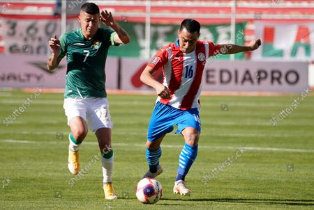 Bolivia's Juan Carlos Arce, left, fights for the ball with Paraguay's Ángel Cardozo Lucena during a qualifying soccer match for the FIFA World Cup Qatar 2022, at Hernando Siles stadium in La Paz, Bolivia