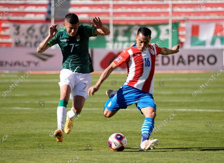 Paraguay's Ángel Cardozo Lucena, right, prepares to strike the ball as Bolivia's Juan Carlos Arce follows him during a qualifying soccer match for the FIFA World Cup Qatar 2022, at Hernando Siles stadium in La Paz, Bolivia