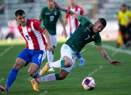 Bolivia's Juan Carlos Arce, right, fights for the ball with Paraguay's Richard Sanchez during a qualifying soccer match for the FIFA World Cup Qatar 2022, at Hernando Siles stadium in La Paz, Bolivia