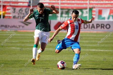 Juan Carlos Arce (L) of Bolivia vies for the ball with Angel Cardozo of Paraguay during  the South American soccer qualifers to Qatar 2022 World Cup between Bolivia and Paraguay at Hernando Siles stadium in La Paz, Bolivia, 14 October 2021.