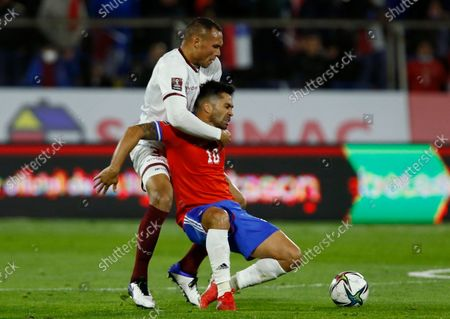 Chile's Luis Jimenez, right, is challenged by Venezuela's Adrian Martinez during a qualifying soccer match for the FIFA World Cup Qatar 2022 at San Carlos de Apoquindo stadium in Santiago, Chile