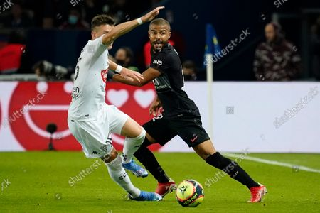 Stock Photo of Rafinha of PSG takes on Pierrick Capelle of Angers