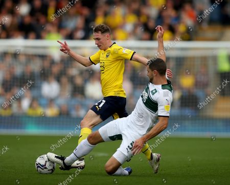 Stock Image of Gavin Whyte of Oxford United is tackled by James Wilson of Plymouth Argyle