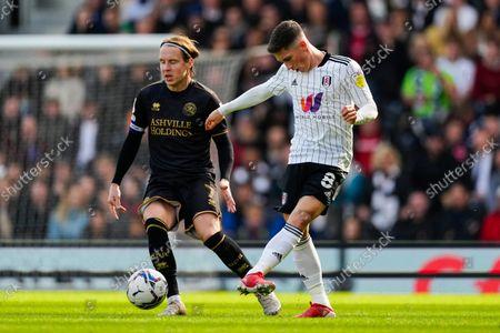 Harry Wilson of Fulham passes the ball past Stefan Johansen of QPR