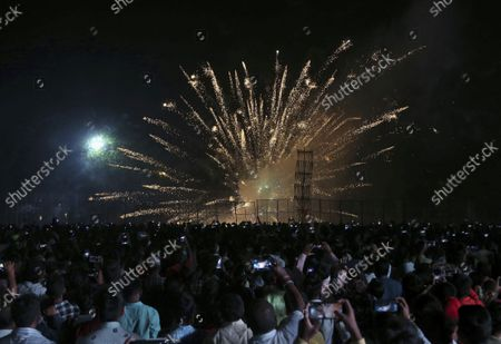People watch fireworks before the burning of an effigy of demon king Ravana, marking the end of Dussehra festival in Hyderabad, India, . Dussehra commemorates the triumph of Lord Rama over the demon king Ravana, marking the victory of good over evil