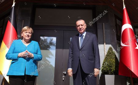 Turkish President Recep Tayyip Erdogan, right, and German Chancellor Angela Merkel pose for photos before their meeting, in Istanbul, . Merkel and Erdogan are expected to discuss Ankara's relationship with Germany and the European Union as well as regional issues including Syria and Afghanistan. The chancellor's trip is one of her last before she leaves her position
