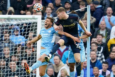 Manchester City's Ruben Dias, left, jumps for the ball with Burnley's Nathan Collins during the English Premier League soccer match between Manchester City and Burnley at Etihad stadium in Manchester, England
