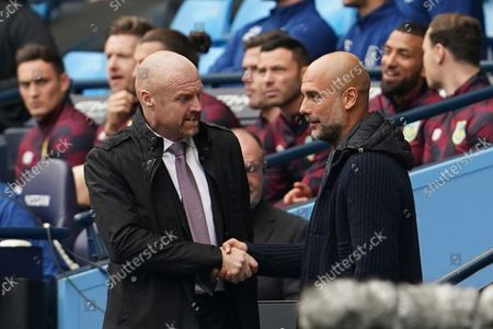 Manchester City's head coach Pep Guardiola, right, cheers Burnley's manager Sean Dyche during the English Premier League soccer match between Manchester City and Burnley at Etihad stadium in Manchester, England