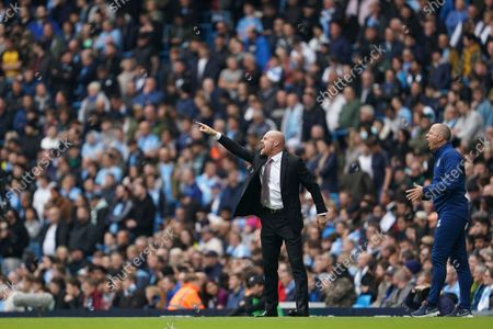 Burnley's manager Sean Dyche, left, shouts out from the touchline during the English Premier League soccer match between Manchester City and Burnley at Etihad stadium in Manchester, England