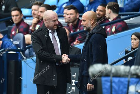 Manchester City manager Pep Guardiola (R) and Burnley manager Sean Dyche (L) shakes hands before the English Premier League soccer match between Manchester City and Burnley in Manchester, Britain, 16 October 2021.