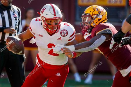 Minnesota defensive lineman Esezi Otomewo (9) drags Nebraska quarterback Adrian Martinez (2) into the end zone where he intentionally grounded the ball resulting in a safety in the fourth quarter of an NCAA college football game, in Minneapolis. Minnesota won 30-23