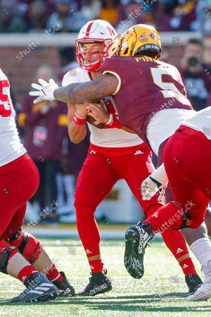 Minnesota defensive lineman Nyles Pinckney (5) sacks Nebraska quarterback Adrian Martinez (2) in the first quarter of an NCAA college football game, in Minneapolis. Minnesota won 30-23