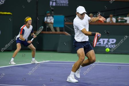 Andrey Rublev, left, of Russia, waits while partner Aslan Karatsev, also of Russia, hits the ball to John Peers, of Australia, and Filip Polasek, of Slovakia, in the men's doubles final at BNP Paribas Open tennis tournament, in Indian Wells, Calif