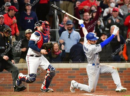 Los Angeles Dodgers second baseman Trea Turner (R) strikes out in front of Atlanta Braves catcher Travis d'Arnaud (L) with a runner on third base to end the seventh inning in game one of the MLB NLCS at Truist Park on October 16, 2021, in Atlanta, Georgia.