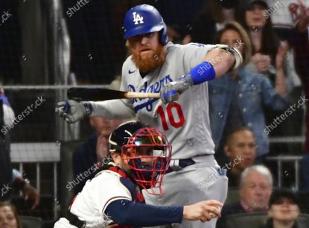 Atlanta Braves catcher Travis d'artaud (L) looks for a ruling on Los Angeles Dodgers Justin Turner swing on a third strike to end the first inning Dodgers Corey Seager left on second base in game one of the MLB NLCS at Truist Park on October 16, 2021 in Atlanta, Georgia.