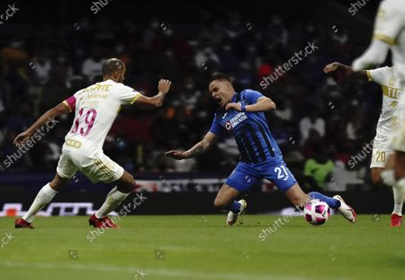 Stock Image of Cruz Azul's Jonathan Rodriguez, center, falls on the pitch between Tigres' Guido Pizarro, left, and Javier Aquino during a Mexican Soccer League match at Azteca stadium in Mexico City