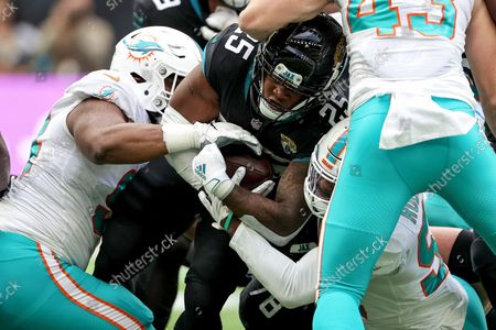 Stock Image of Jacksonville Jaguars vs Miami Dolphins. Jacksonville Jaguars' James Robinson is tackled by Christian Wilkins and Elandon Roberts of the Miami Dolphins