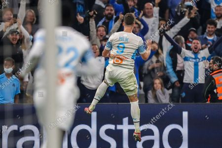 Marseille's Arkadiusz Milik celebrates after scoring his side's third goalduring the French League One soccer match between Marseille and FC Lorient at the Velodrome stadium in Marseille, France