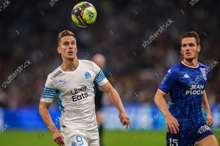 Marseille's Arkadiusz Milik, left, vies for the ball with Lorient's Julien Laporte during the French League One soccer match between Marseille and FC Lorient at the Velodrome stadium in Marseille, France