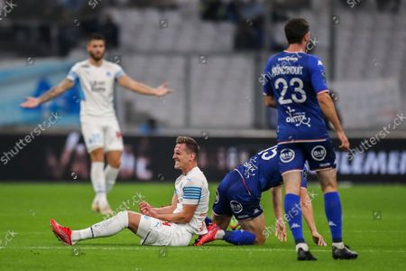 Stock Image of Marseille's Arkadiusz Milik, second left, grimaces in pain during the French League One soccer match between Marseille and FC Lorient at the Velodrome stadium in Marseille, France