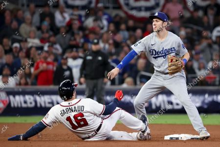 Los Angeles Dodgers second baseman Trea Turner, right, throws to first after forcing out Atlanta Braves' Travis d'Arnaud to complete a double play during the seventh inning in game two in the 2021 National League Championship Series forcing out Dansby Swanson at Truist Park on Sunday, Oct. 17, 2021 in Atlanta, GA.(Robert Gauthier / Los Angeles Times)