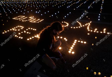 (211019) - TEL AVIV, Oct. 19, 2021 (Xinhua) - A woman lights candles during a memorial event commemorating the 26th anniversary of the assassination of former Israeli Prime Minister Yitzhak Rabin in central Israeli city of Tel Aviv on Oct. 18, 2021. Israel marked the 26th anniversary of the assassination of former Prime Minister Yitzhak Rabin, who was shot dead by a far-right Jewish man as he strived for peace with the Palestinians.