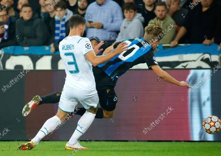 Brugge's Charles De Ketelaere, right, goes down after being challenged by Manchester City's Ruben Dias during the Champions League Group A soccer match between Club Brugge and Manchester City at the Jan Breydel stadium in Bruges, Belgium