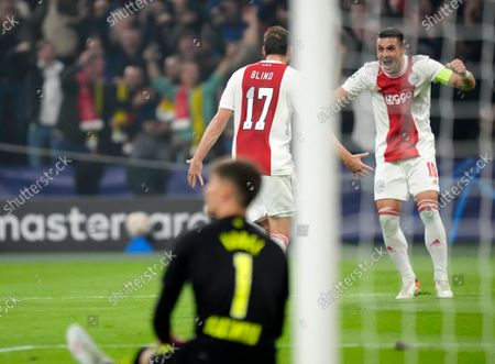 Ajax's Daley Blind, center, celebrates with Ajax's Dusan Tadic after scoring his side's second goal during the Champions League group C soccer match between Ajax and Borussia Dortmund at the Johan Cruyff ArenA in Amsterdam, Netherlands