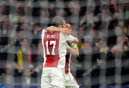 Ajax's Daley Blind, left, celebrates with Ajax's Dusan Tadic after scoring his side's second goal during the Champions League group C soccer match between Ajax and Borussia Dortmund at the Johan Cruyff ArenA in Amsterdam, Netherlands