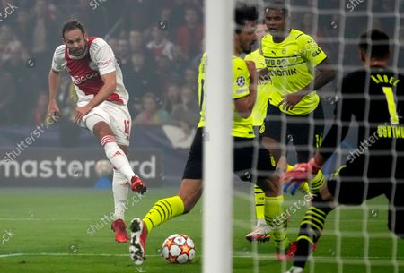 Ajax's Daley Blind, left, kicks the ball during the Champions League group C soccer match between Ajax and Borussia Dortmund at the Johan Cruyff ArenA in Amsterdam, Netherlands